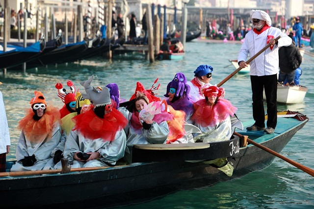 January 24, 2015 - Venice, Italy: Boats sail along the Grand Canal during the water parade, part of the Venice Carnival.The Venice carnival in the historical lagoon city attracts people from around the world. (Manuel Silvestri/Polaris).